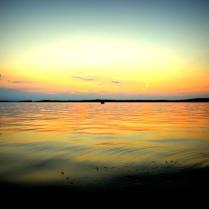 Nydelig solnedgang over stille vann på fjorden