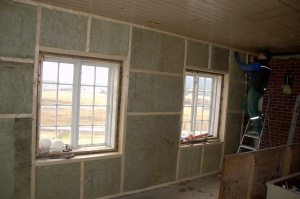 Det ytterste laget med nyere plater er fjernet, veggen er lektet ut og  isolert