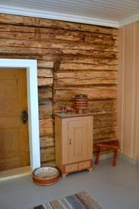 1700-tallsdøra mellom stua og soverommet har fått selskap av et gammelt skap, en dnydelig dekorert grøtdall, en mjølkebunk og en trebenet fjøskrakk.