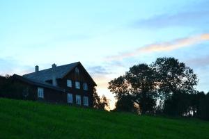 Vi liker silhuetten av huset og de gamle lindetrærne mot solnedgangen