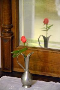 Rosene holder fortsatt stand mot høstkulda. Denne enslige blomsten gjør seg fint i den gamle tinnvasen.