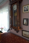 - et gammelt veggur og fotografier på veggene gjør det hjemmekoselig