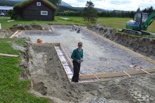 Nytt hus skal opp på gården, og gravearbeidet er foretatt. Vi venter på tømrerne som skal sette opp den gamle tømmerbygningen, kaffekvernhuset.