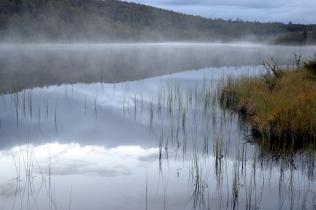 Skyene har forsvunnet og vannet ligger speilblankt. Litt tåke kommer svevende over vannet