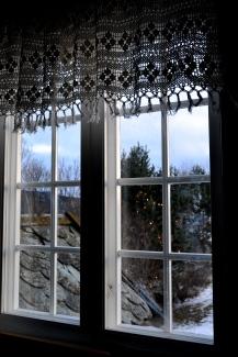 Lys i treet utenfor skimtes gujennom vinduet i storstua